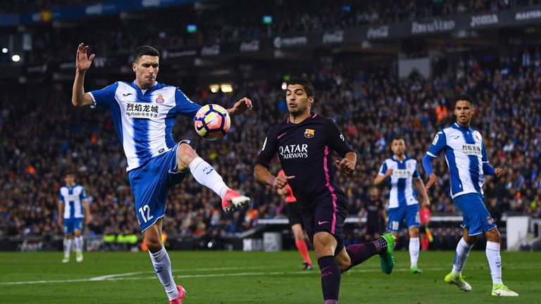 Aaron Martin of RCD Espanyol competes for the ball with Luis Suarez of FC Barcelona during the La Liga match