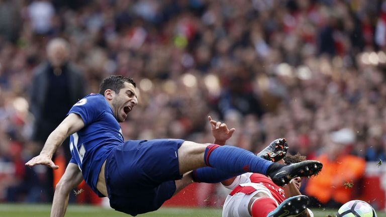 Henrikh Mkhitaryan is challenged by Alex Oxlade-Chamberlain