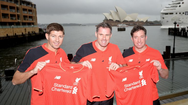 Former Liverpool football stars Steven Gerrard (L) Jamie Carragher (C) and Robbie Fowler (R) hold up Liverpool shirts in front of Sydney Harbour in Sydney