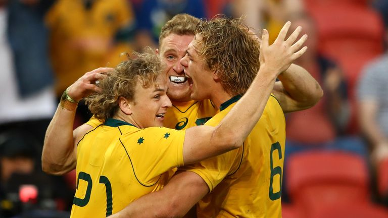Reece Hodge of the Wallabies celebrates with team-mates after his try against Italy
