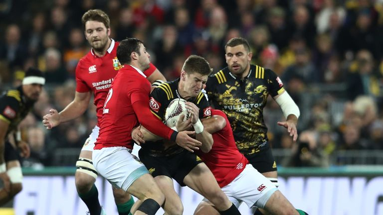 Hurricanes' Jordie Barrett is tackled by Lions duo Robbie Henshaw and Rory Best