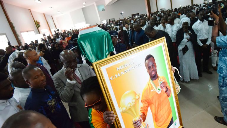 Pallbearers carry the coffin of football star Cheick Tiote during his funeral