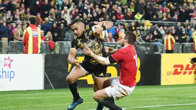 Ngani Laumape of the Hurricanes breaks a tackle by Dan Biggar
