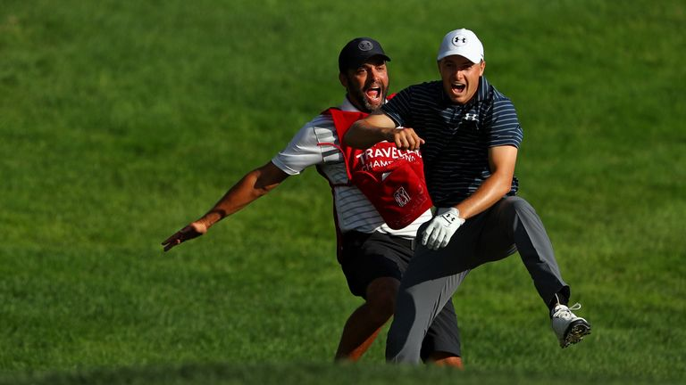 Jordan Spieth celebrates with caddie Michael Greller after chipping in for birdie from a bunker on the 18th
