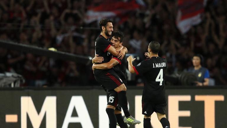 Hakan Calhanoglu (L) celebrates scoring against Bayern Munich