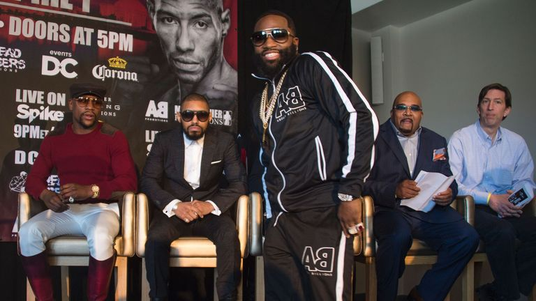 WBA super lightweight champion Adrien Broner (C) smiles as he walks past his upcoming opponent Ashley Theophane (2nd L) as promoter and former champion box