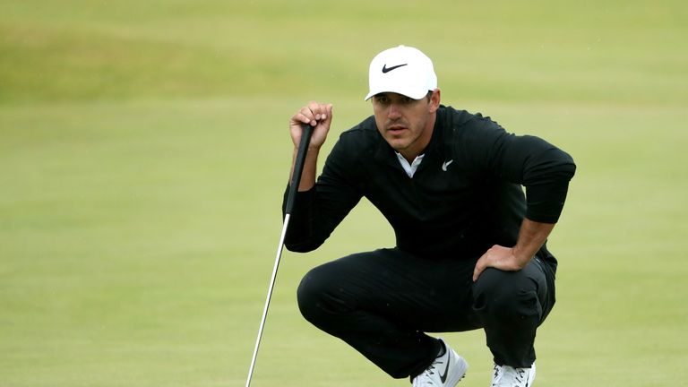 Koepka lines up a putt on the fifth green