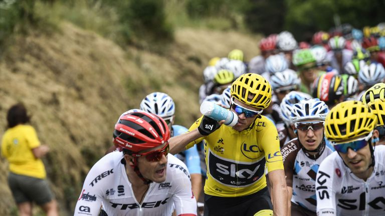 Great Britain's Christopher Froome (C), wearing the overall leader's yellow jersey, drinks as he rides during the 222,5 km nineteenth stage of the 104th ed