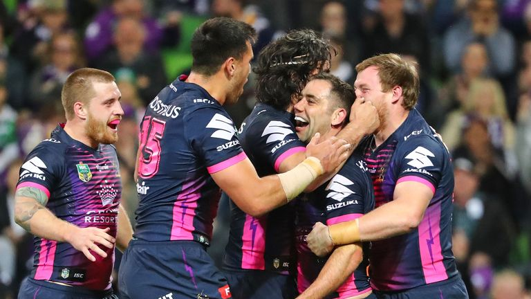Cameron Smith of the Storm is congratulated by his team-mates  after scoring a try against the Rabbitohs