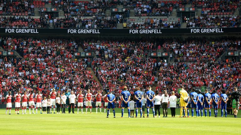Both teams stand to remember the victims of the Grenfell Tower fire