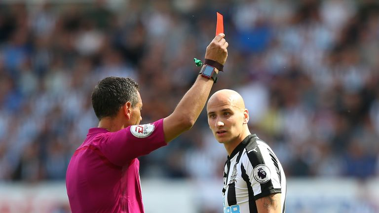 Andre Marriner shows a red card to Jonjo Shelvey after his stamp on Dele Alli