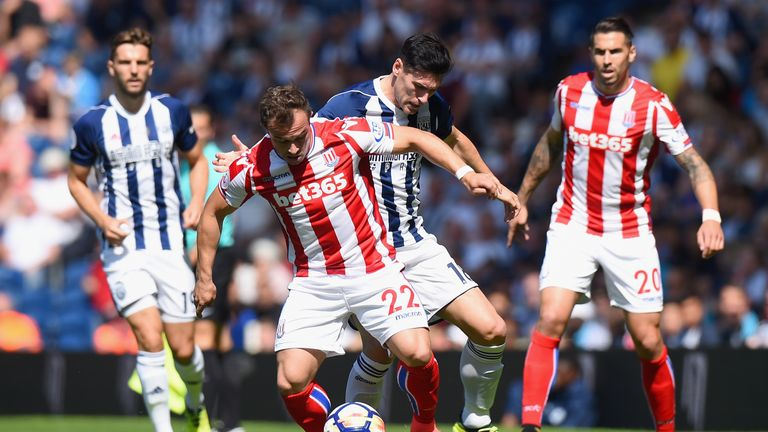 Xherdan Shaqiri and Gareth Barry challenge for the ball in the first half
