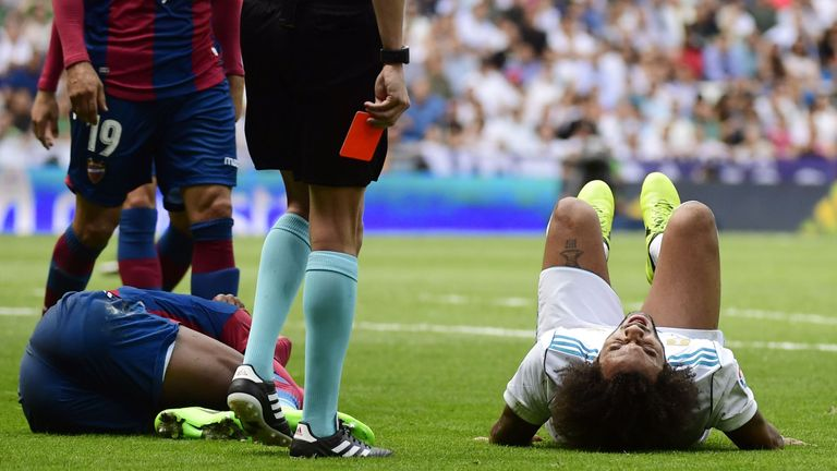 The referee waits with his red card as Marcelo lies on the ground after colliding with, and then kicking, Jefferson Lerma