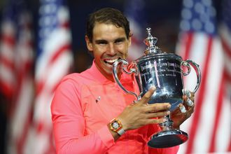 Rafael Nadal of Spain bites the championship trophy