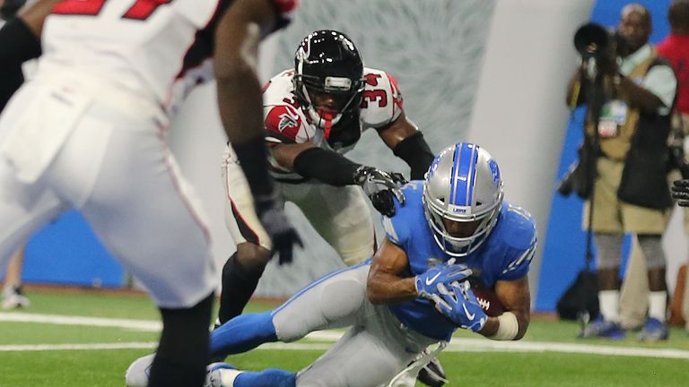 DETROIT, MI - SEPTEMBER 24:  Golden Tate #15 of the Detroit Lions catches the ball as Brian Poole #34 of the Atlanta Falcons touches him and his knee hits