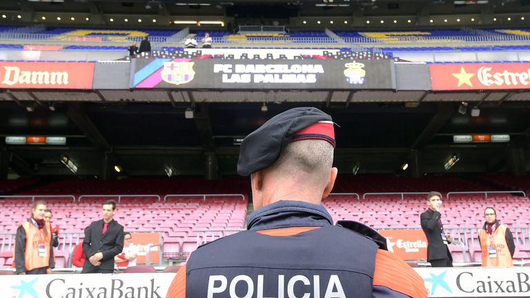 A police officer stands in front of empty stands after the decision to play the game behind closed doors