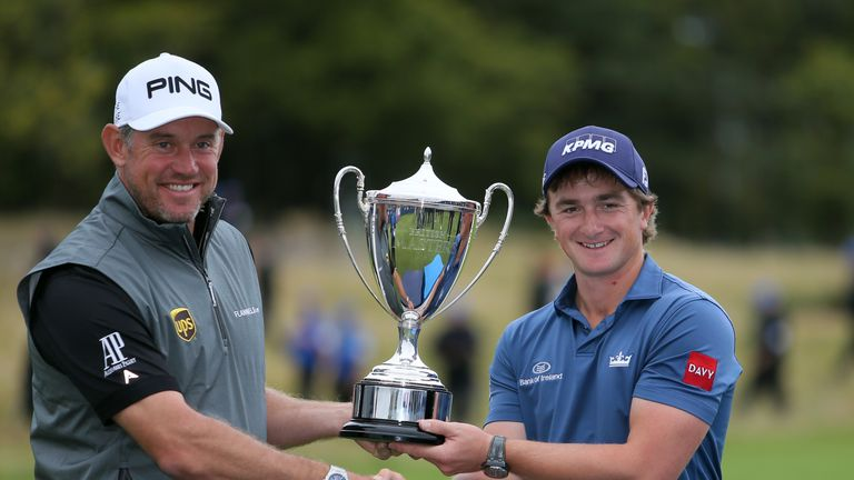 Dunne receives the trophy from tournament host Lee Westwood