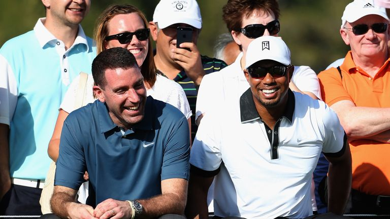 Tiger Woods jokes with his agent Mark Steinberg (left)