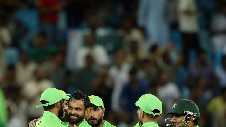 DUBAI, UNITED ARAB EMIRATES - OCTOBER 13:  Mohammad Hafeez of Pakistan celebrates with teammates after dismissing Upul Tharanga of Sri Lanka during the fir
