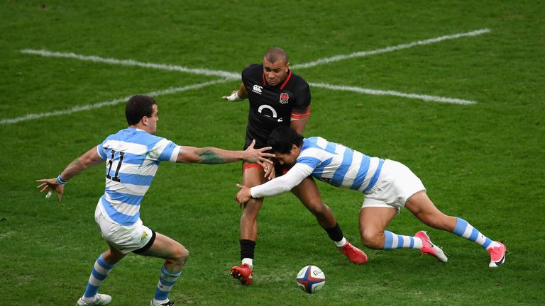 Jonathan Joseph dinks the ball ahead as he is tackled by  Emiliano Boffelli