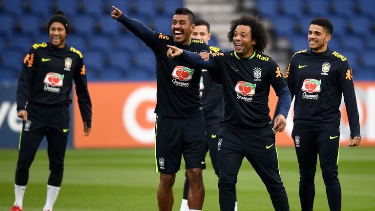 Brazil's midfielder Paulinho (L) jokes with defender Marcelo during a training session