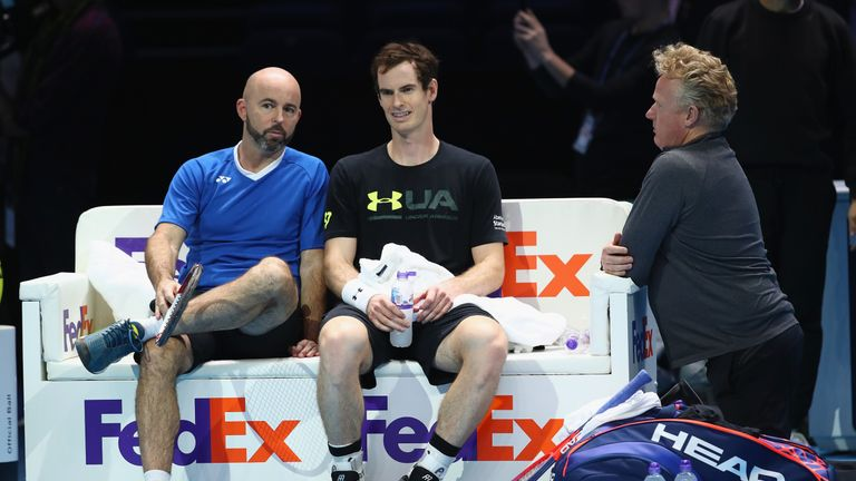 Andy Murray of Great Britain and coach Jamie Delgado talk as physio Mark Bender listens