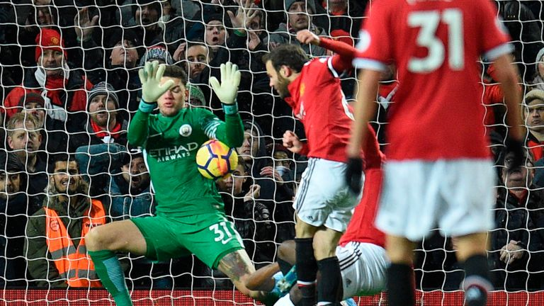 Man City 'keeper Ederson (left) prevents Juan Mata from equalising late on