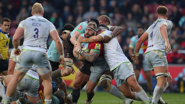 Joe Marler of Harlequins is tackled by fellow England international Jamie George