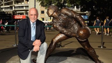 Ken Catchpole poses with a sculpture of him outside Sydney Football Stadium in 2010