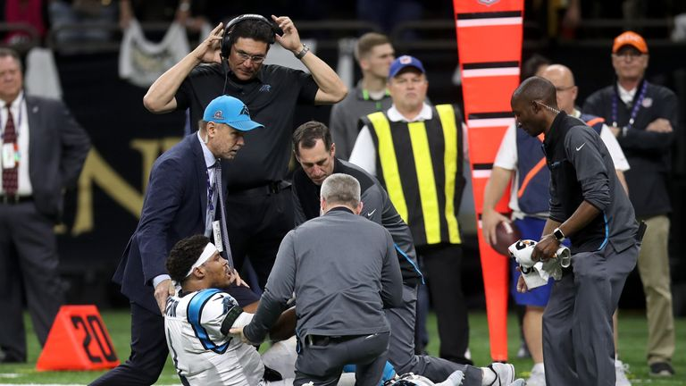 Cam Newton is checked by Carolina Panthers medical staff after a heavy hit