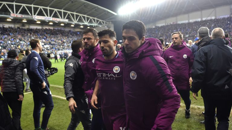 WIGAN, ENGLAND - FEBRUARY 19:  Sergio Aguero of Manchester City looks dejected as he leaves the pitch with assistant coach Mikel Arteta after the Emirates