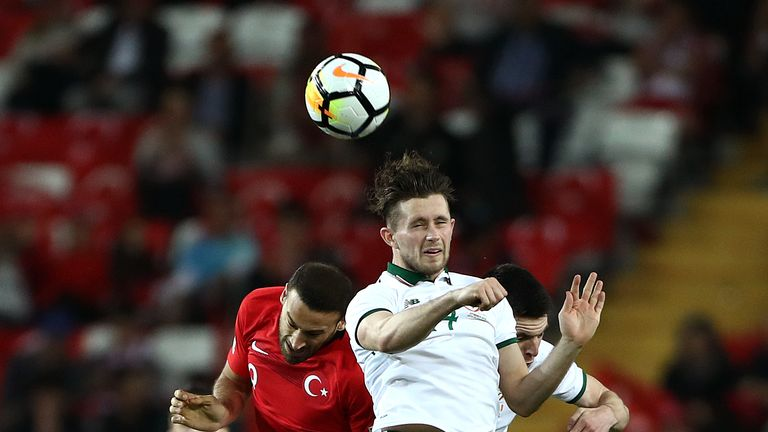 Alan Browne and Cenk Tosun go up for the ball during the match