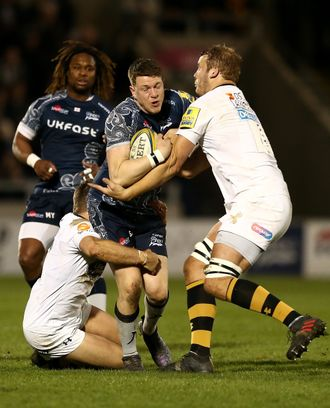 Sam James of Sale is tackled by Jimmy Gopperth and Joe Launchbury of Wasps
