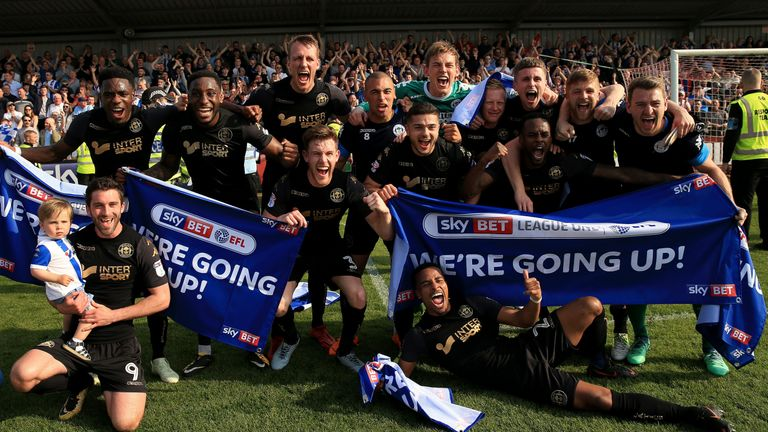 """The Wigan Athletic team celebrate their promotion to the EFL Championship during the Sky Bet League One match at Highbury Stadium, Fleetwood. PRESS ASSOCIATION Photo. Picture date: Saturday April 21, 2018. See PA story SOCCER Fleetwood. Photo credit should read: Clint Hughes/PA Wire. RESTRICTIONS: EDITORIAL USE ONLY No use with unauthorised audio, video, data, fixture lists, club/league logos or """"live"""" services. Online in-match use limited to 75 images, no video emulation. No use in betting, games or single club/league/player publications."""