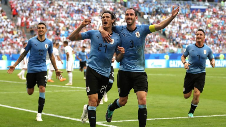 Edinson Cavani celebrates with team-mate Diego Godin after scoring Uruguay's third goal