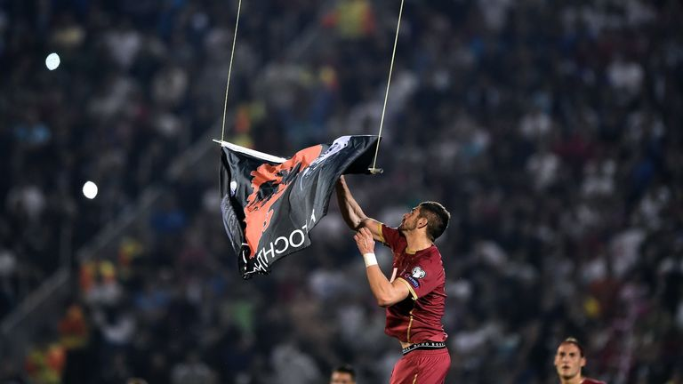 Serbia defender Stefan Mitrovic grabs a flag flown by the remotely-operated drone