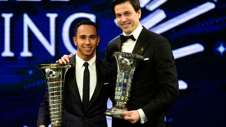 Mercedes' Lewis Hamilton and Toto Wolff with their respective Drivers' and Constructors' World Championship trophies (FIA image)