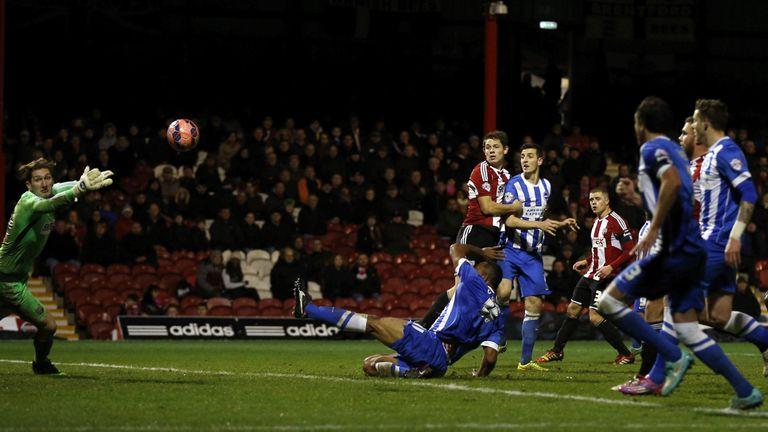 Lewis Dunk scores the opener for Brighton against Brentford