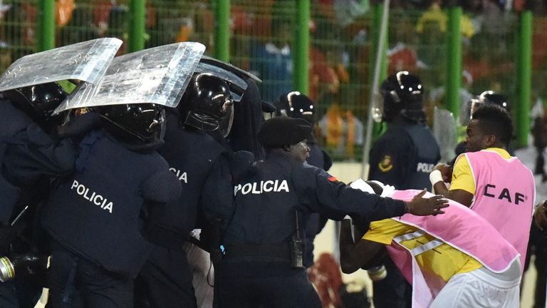 Ghana players leave the pitch protected by riot police