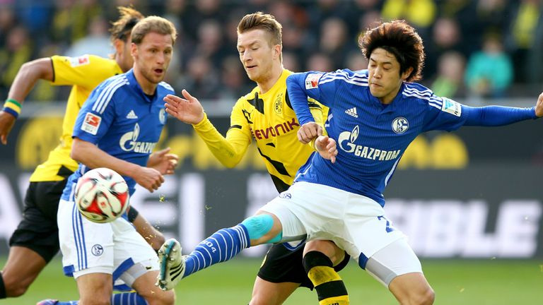 Marco Reus of Dortmund battles for the ball with Atsuto Uchida