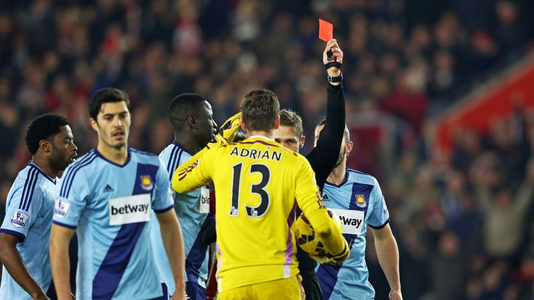 Adrian of West Ham receives a red card from referee Craig Pawson after diving on the ball outside of the area