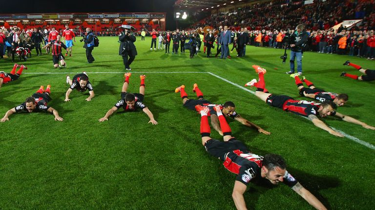 Bournemouth players celebrate promotion with a formation dive.