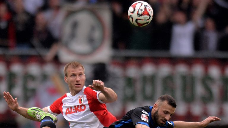 Ragnar Klavan of Augsburg battles for a header with Sueleyman Coc
