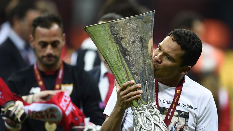 Sevilla forward Carlos Bacca kisses the trophy