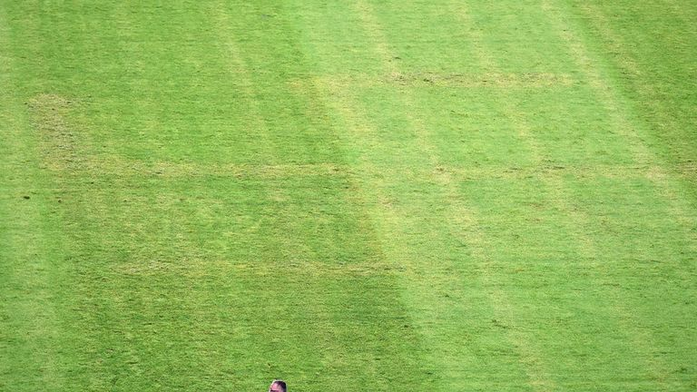 A man looks at the pitch appearing to show the pattern of a swastika following the the Euro 2016 qualifying football match between Croatia and Italy