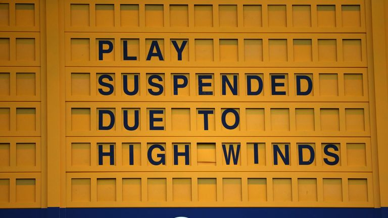 A scoreboard displays that play is suspended due to high winds