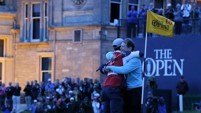 Watson (R) hugs his caddie, son Michael on the 18th green