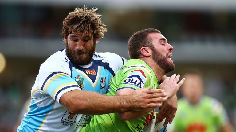 David Taylor of the Gold Coast Titans (left) tackles Mark Nicholls of the Canberra Raiders in an NRL clash