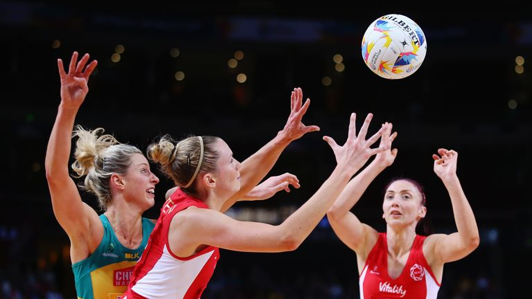 Jo Harten of England (middle) battles for the ball with Australia's Laura Geitz (left)