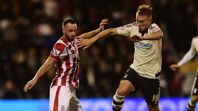 Cauley Woodrow of Fulham is tackled by Marc Wilson of Stoke